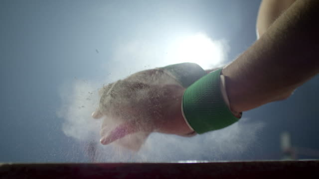 Sportsman chalking his hands before performance . Shot on RED EPIC Cinema Camera in slow motion. video