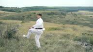Sportsman exercising moves of taekwondo on the nature. Slowly video