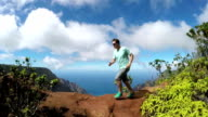 SLOW MOTION: Sportsman jogging in jungle mountains overlooking valley and ocean video
