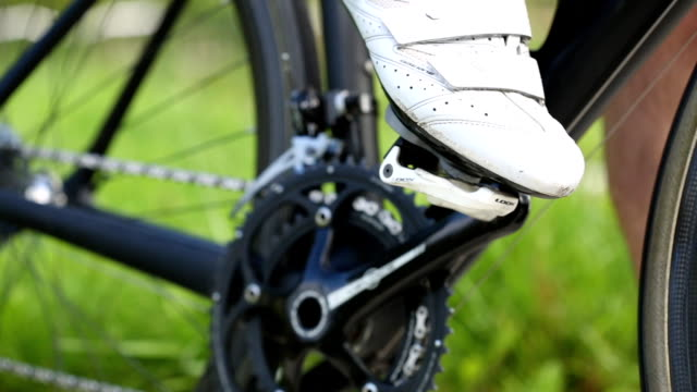 Sportsman puts his foot on the pedal of his of black road bicycle. Close up shot video