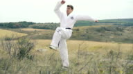 Sportsman shows moves of taekwondo on the nature. Slowly video