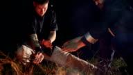 Sportsmen doing moves over bonfire on thr night. Slow motion video
