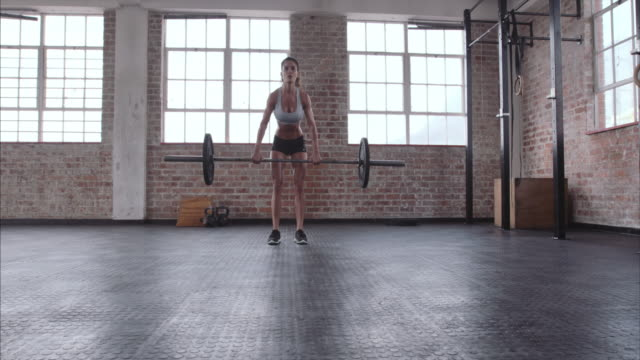 Sportswoman doing weight lifting workout video