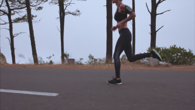 Sportswoman jogging on countryside road in morning video