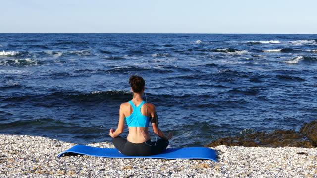 4K Sportswoman practicing yoga on beach video
