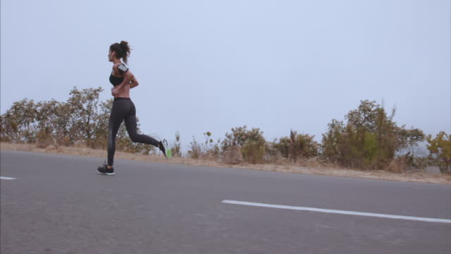 Sportswoman running on country road in morning video