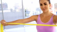 Sportswoman stretching a yellow band video