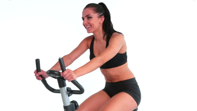 Sporty cheerful brunette using exercise bike video