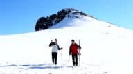 Sporty couple walking down the ski slope video