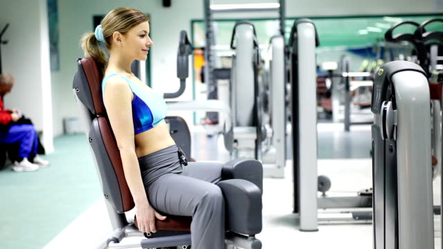 Sporty girl exercising in a fitness center. video