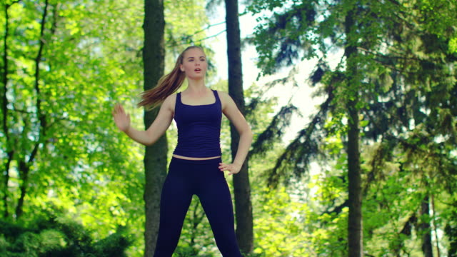 Sporty woman doing fitness exercises outdoor. Female runner stretching video