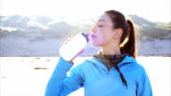 Sporty woman drinking water on beach after run video