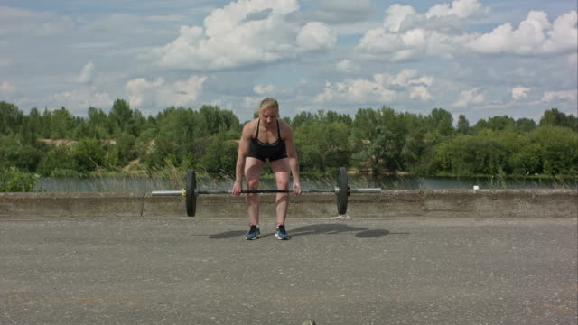 Sporty woman exercising with barbell over city waterside background video