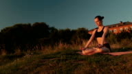 Sporty woman in lotus position in the park at sunset video