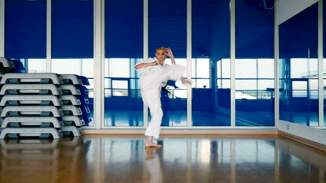 Sporty woman in white kimono practicing the karate tricks in the gym video