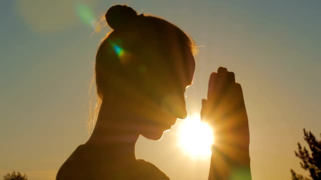 Sporty woman praying in forest at sunset video