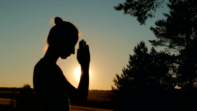 Sporty woman praying in park at sunset video