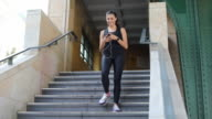 Sporty woman using smart phone on steps video
