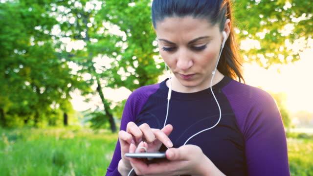 Sporty woman using smart phone. video
