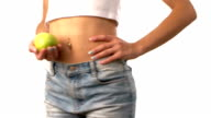 Sporty woman with apple in her hand, spinning, on white background video