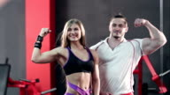 Sporty young couple posing and showing off their biceps video