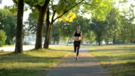 Sporty young woman running on sidewalk in morning video
