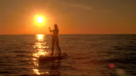 AERIAL: Sporty young woman stand up paddle boarding on sunny summer evening video