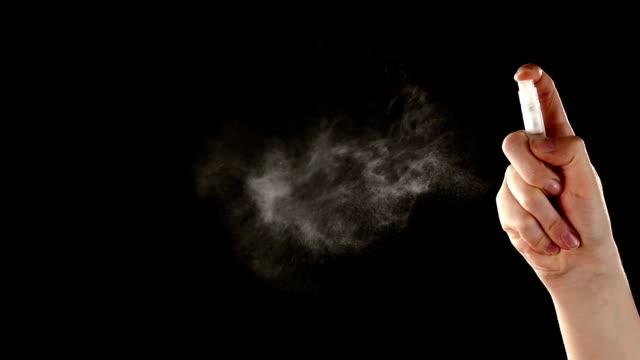 Spray bottle drops like perfume on black, slow motion video