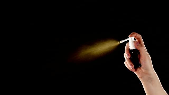 Spray drops of medicine on black, slow motion video