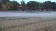 Sprayer equipment spray herbicides chemicals on field. Follow. video