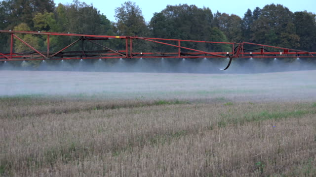 Sprayer equipment spray herbicides chemicals on field. Follow. video