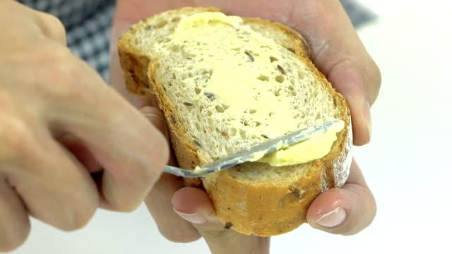 Spreading butter on baguette, bread, slow video