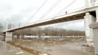 Spring river with dirty brown water and ice. floating of ice and bridge video
