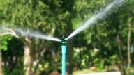 Sprinkler spray water over green fields,Slow motion video