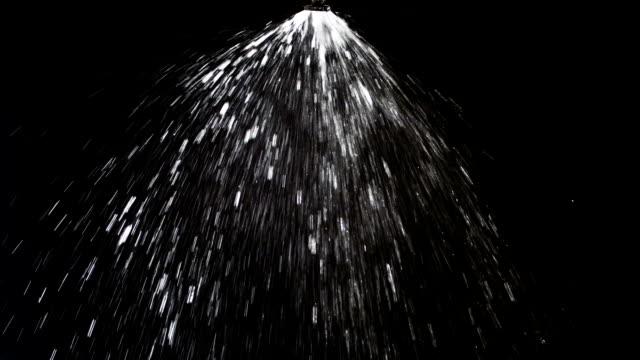 Sprinkler sprinkling water on black background video