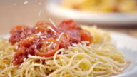 SLO MO sprinkling parmesan over spaghetti with tomato sauce video