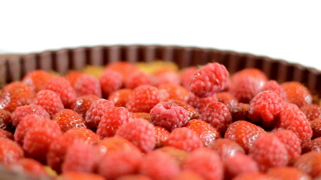 Sprinkling sugar onto rotating fruit tart video