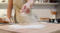 SLO MO Sprinkling the flour over wooden board with hand video