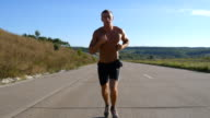Sprinting runner man jogging at highway. Male sport athlete training outdoor at summer. Young strong muscular guy exercising on rural road during workout. Active healthy lifestyle outside. Close up video