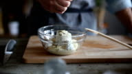 Squeezing lemon in bowl for salad dressing video