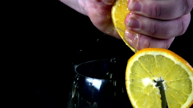 HD SLOW: Squeezing orange into a glass on black background video