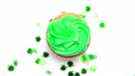 St patricks day cupcake revolving with green shamrock confetti falling video