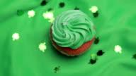 St patricks day cupcake revolving with shamrock confetti falling video