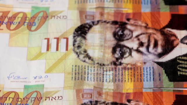 Stack of Israeli money bills of one hundred shekel - Tilt down video