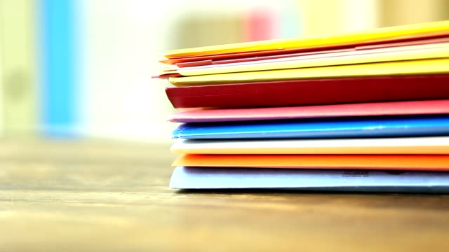 Stack of multi colored file folders on a desk in an office. video