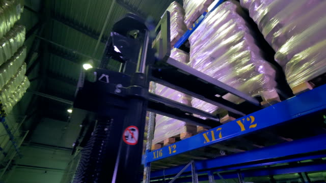 A stackers forks moving from a shelved cargo pallet. video