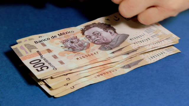Stacking Mexican Peso Money In the 500 denomination. video