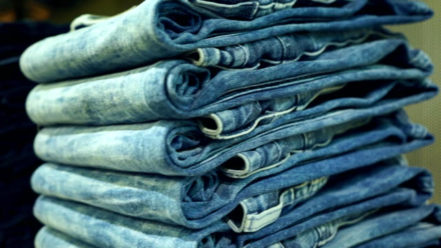 Stacks of new blue jeans in the store pan shot video