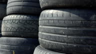 Stacks of old used car tyres FullHD zoom in shot. Disposal site video