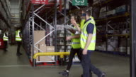 Staff walking though warehouse with manager, shot on R3D video